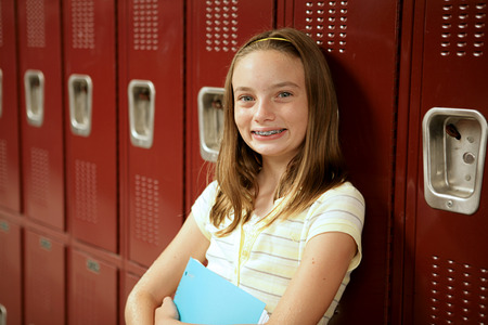 An adorable teen girl with braces and freckles standing in front of her locker. Stock Photo - 1470005