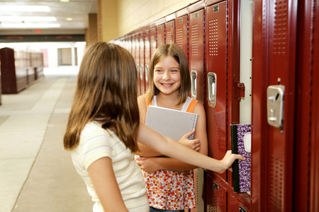 Middle school girls gossiping at their lockers.