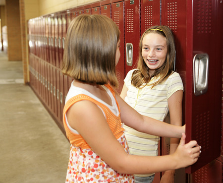 Two middle school students chatting at their lockers.   版權商用圖片