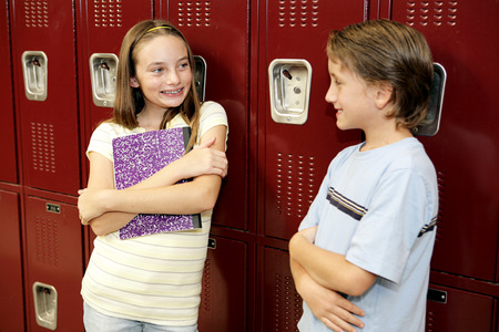A boy and a girl in school, chatting by their lockers.