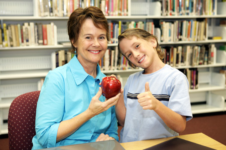 A school boy giving an apple to his teacher and a thumbsup sign to the camera. Stock Photo - 1470014