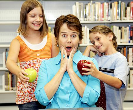 A teacher surprised by two students with apples for her. Stock Photo - 1470004