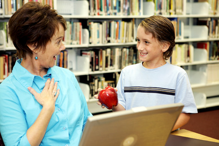 A school boy surprising his teacher with an apple. Stock Photo - 1470011