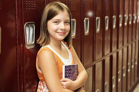 A pretty school girl leaning against her locker. photo