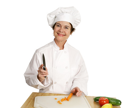 A friendly chef smiling at the camera as she prepares to chop vegetables.  Isolated on white. Stock Photo - 1497975