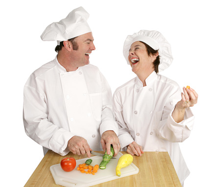 goofing: Two chefs goofing around and laughing in the kitchen as they work.  Isolated on white.