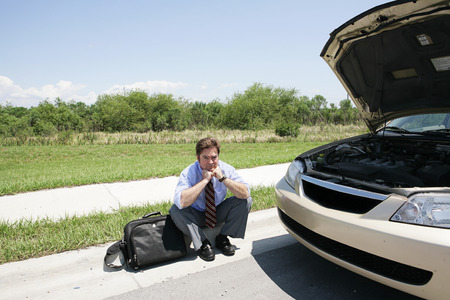A sad looking businessman sitting on the curb waiting for the motor club. Stock Photo - 1518609