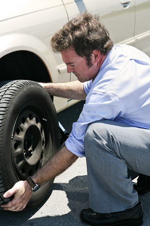 inconvenient: A businessman changing a flat tire on the road, red faced from the heat.   Stock Photo