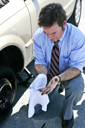 A businessman wiping his dirty hands off after changing a tire.   Stock Photo