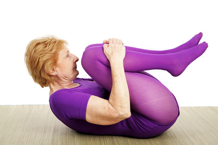 A fit flexible seventy year old woman doing a suppine yoga pose.  White background Stock Photo
