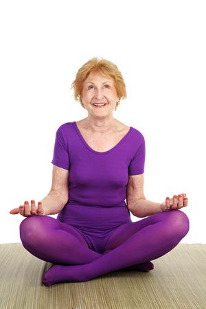 Een fit zeventig jaar oude vrouw in een gewijzigde yoga pose lachend in tevredenheid. Witte achtergrond.