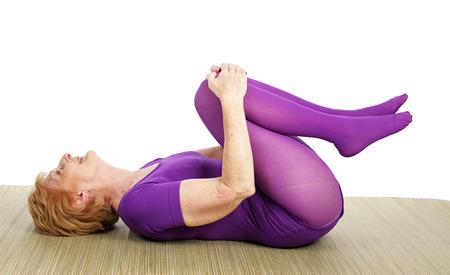 seventy: Fit settanta anni di et� donna gode di fare yoga. Sfondo bianco.