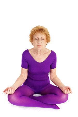 A fit seventy year old woman meditating during a yoga practice.  White background.