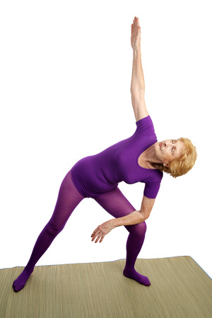 A senior woman in her seventies doing the modified triangle pose in yoga.  Isolated on white. photo