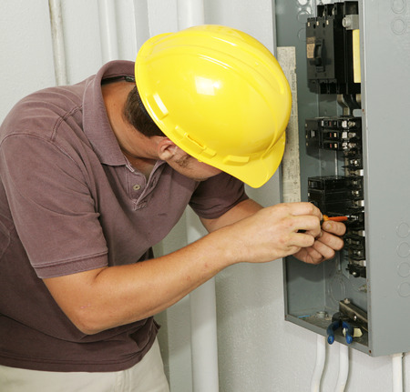 An electrician working on an electrical breaker panel.  Model is an actual electrician - all work is being performed according to industry codes and safety standards. Stock Photo - 1573339