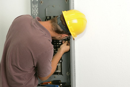 An electrician working on an electrical panel, connecting a wire to a breaker.  Model is an actual electrician and all work performed is in accordance with industry standard safety and code regulations. Stock Photo - 1573348
