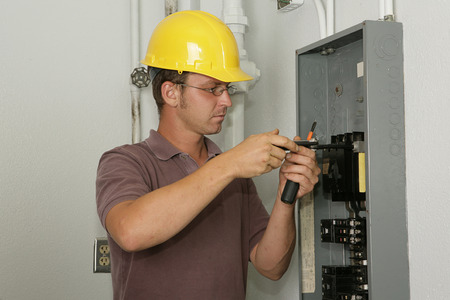 An electrician working on an industrial breaker panel.  Model is an actual electrician performing all work to industry codes and safety standards.