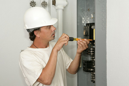 An electrician installing a breaker in an electric panel.  Model is an actual electrician and all work is being performed according to industry codes and safety practices.