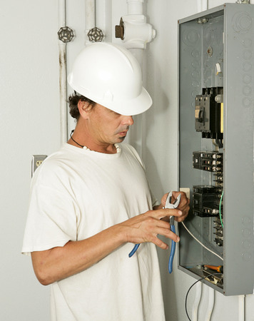 electrical panel: An electrician trimming wire as he hooks up an electrical panel.  Model is an actual electrician and all work is being performed in accordance with industry code and safety standards.   Stock Photo