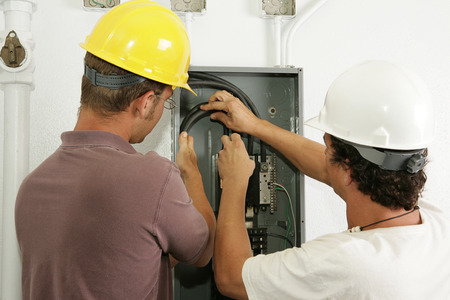 actual: Electricians working together to install a breaker panel.  Models are actual electricians - all work is performed according to industry standard code and safety practices.