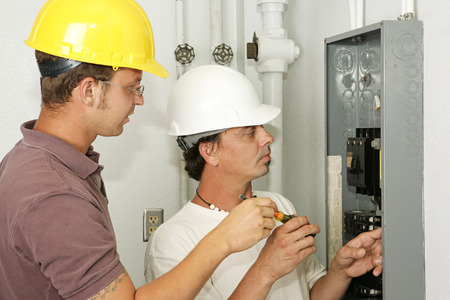 breaker: Electricians wiring an electrical breaker panel.  Models are professional electricians - all work depicted is being performed according to industry codes and safety standards.
