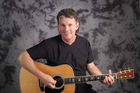 Een knappe, volwassen muzikant met zijn gitaar. Stockfoto