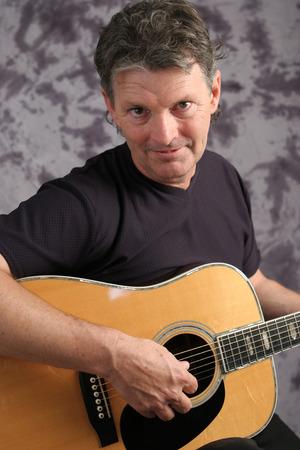 Een portret van een knappe middelbare leeftijd gitarist.