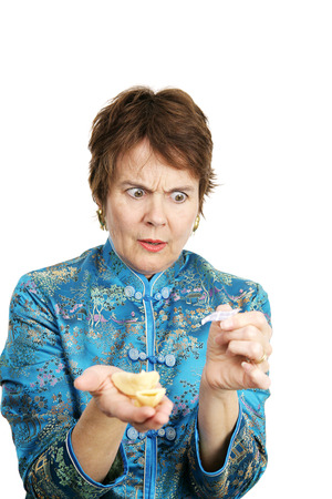 bad fortune: A woman upset over a bad fortune she got in her fortune cookie.  Isolated on white.