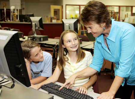 helpful: A helpful teacher showing school kids how to use the computer.