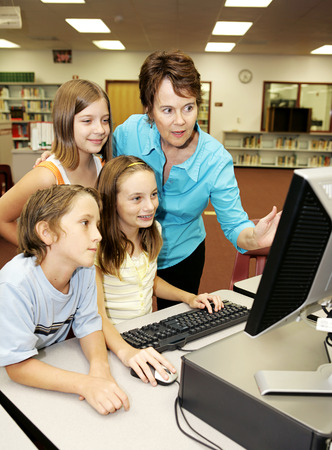 A teacher instructing kids on using the computer.   Stock Photo - 1640209