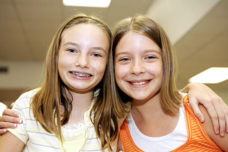 indoors: Two cute adolescent girls together in school.   Stock Photo