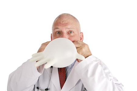 bedside: A silly doctor blowing up his rubber glove.  Isolated on white.