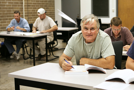 An older adult education student takes school seriously while the younger guys are gooofing off making paper airplanes.