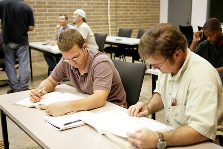 onderwijs: Een volwassen onderwijs klasse doet onderzoek op hun bureau.