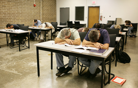 An adult education class sound asleep on their desks.   photo