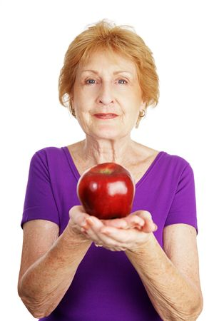 Fit healthy senior lady holding a shiny red apple.   Isolated on white.   photo