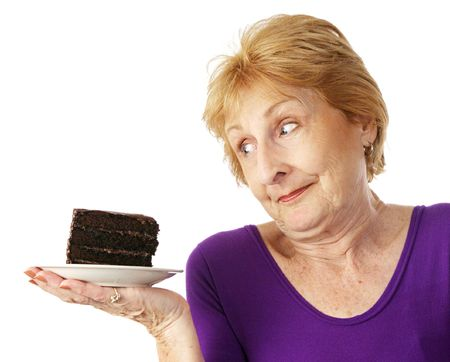 resist: Fit senior woman making food choices.  She is unable to resist the chocolate cake.  Isolated on white.   Stock Photo