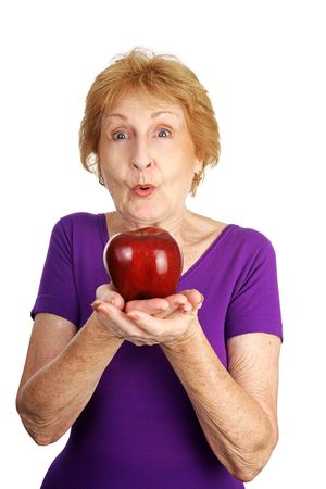 Senior lady excited about the shiny red apple shes about to eat.  Isolated on white.   photo