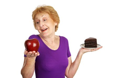 Fit senior lady choosing a healthy apple for dessert instead of fattening chocolate cake. Isolated on white. photo