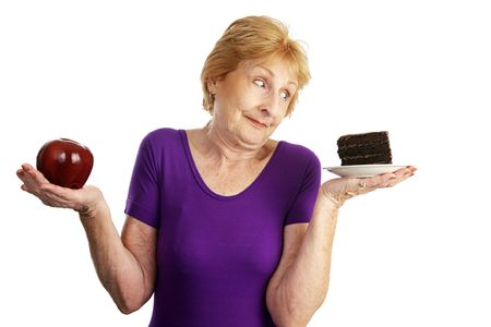 snack: Fit senior woman making food choices.  She is unable to resist the chocolate cake.  Isolated on white.   Stock Photo