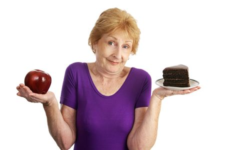 Fit senior woman choosing between chocolate layer cake and an apple for dessert.  Isolated on white.   Stock Photo