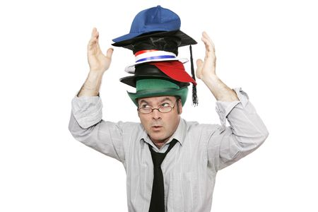 A businessman overwhelmed by too much responsibility - wearing too many hats.  Isolated on white. Stock Photo