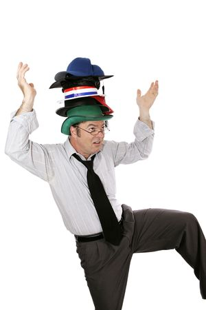 Overwhelmed white collar worker wearing too many hats and balancing on one foot.  Isolated on white. Stock Photo