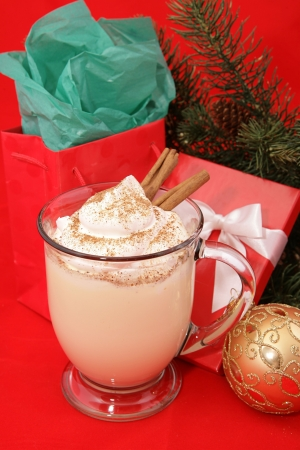 A frothy mug of Christmas eggnog with a dollop of whipped cream, nutmeg and cinnamon sticks, nestled among Christmas gifts and decorations.  Red background. photo