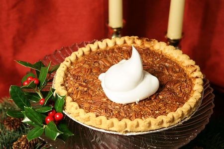 pecan: A delicious pecan pie garnished with holly and a dollop of whipped cream, photographed against a draped red silk background.   Stock Photo