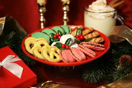 egg nog: A plate of beautiful Christmas cookies and a mug of egg nog on the table beside pine branches and gifts.