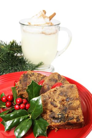 Closeup of delicious Christmas fruitcake garnished with Holly and a mug of egg nog in the background.  Isolated on white.   photo