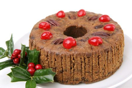 A beautiful Christmas fruitcake garnished with cherries and holly berries.  White background.   photo