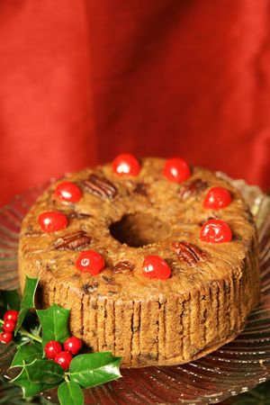 Beautiful Christmas fruitcake with holly garnish on a red draped silk background. Vertical with room for text.   Stock Photo