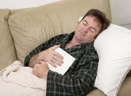 dozing: A man home sick from work has fallen asleep while reading.